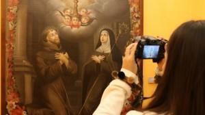 Lourdes Gómez fotografiando una obra en la que se aprecian los estigmas de san Francisco de Asís